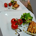 Pan fried goat's cheese terrine with roasted cherry tomatoes on the vine.